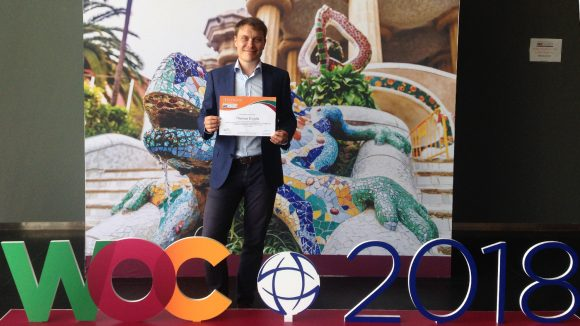 Thomas Engels standing in front of a banner at the World Ophthalmology Congress, holding his certificate.