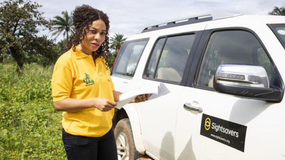 Kareen Atekem is shown in a yellow Sightsavers top standing outside next to a Sightsavers vehicle.