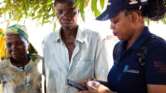 A woman records survey information on a mobile phone app while two survey participant look on.