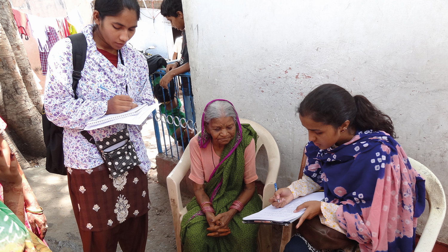 Two female data collectors take information from a woman in Bhopal, India. Two of the women sit on chairs inside and the other stands next to them, writing.
