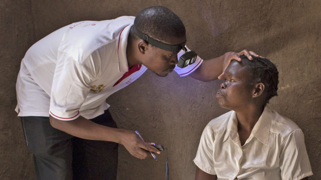 A health worker examines a person's eyes using a headlight. The patient is sitting as he holds her head to examine her eyes.