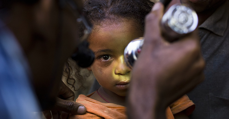 A young child has their eyes examined with a torch.