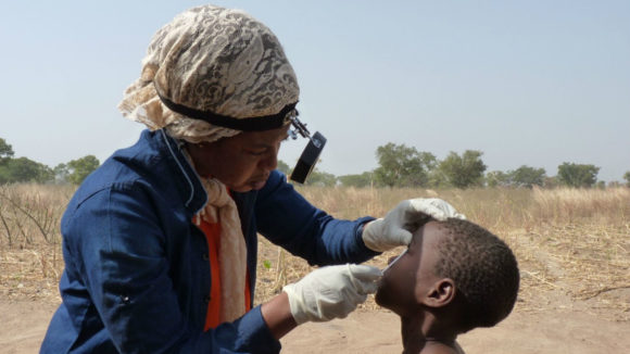 A health worker examines the eyes of a young child outside.