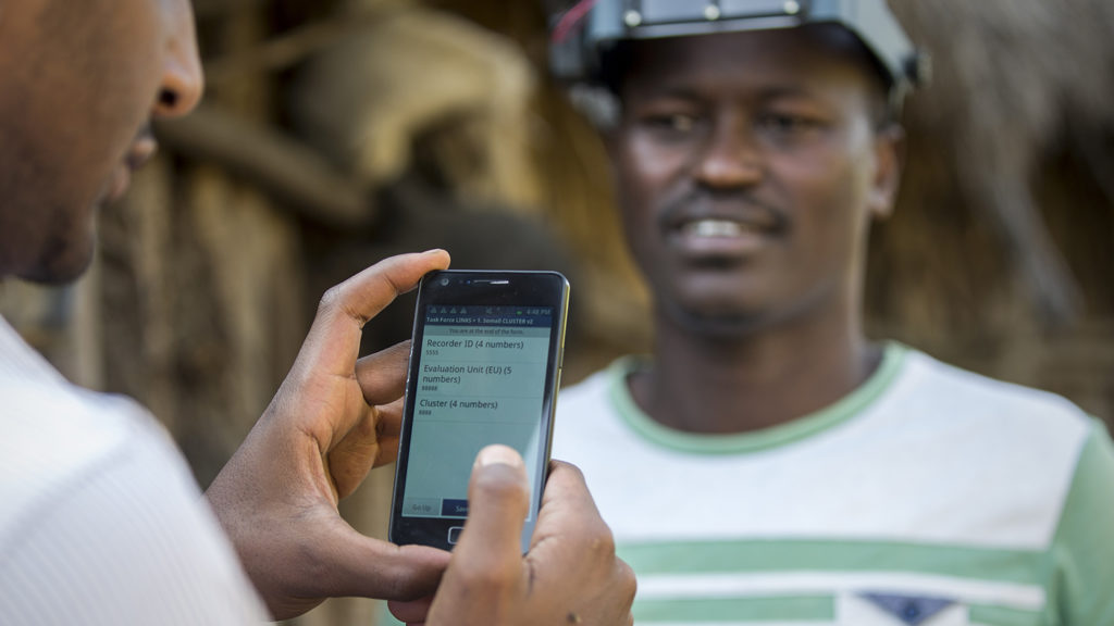 A man research data on a mobile phone.