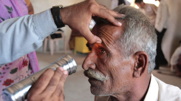 A close up photo of a man having his eyes examined.