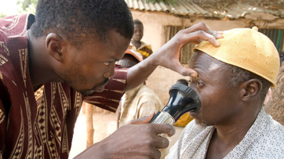 A health worker checks a man's eyes with a torch for signs of infection. They are outside, in front of a house.