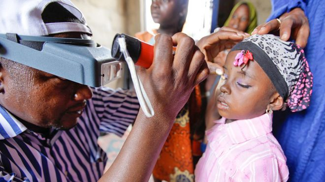 A young girl gets her eyes checked by a health worker