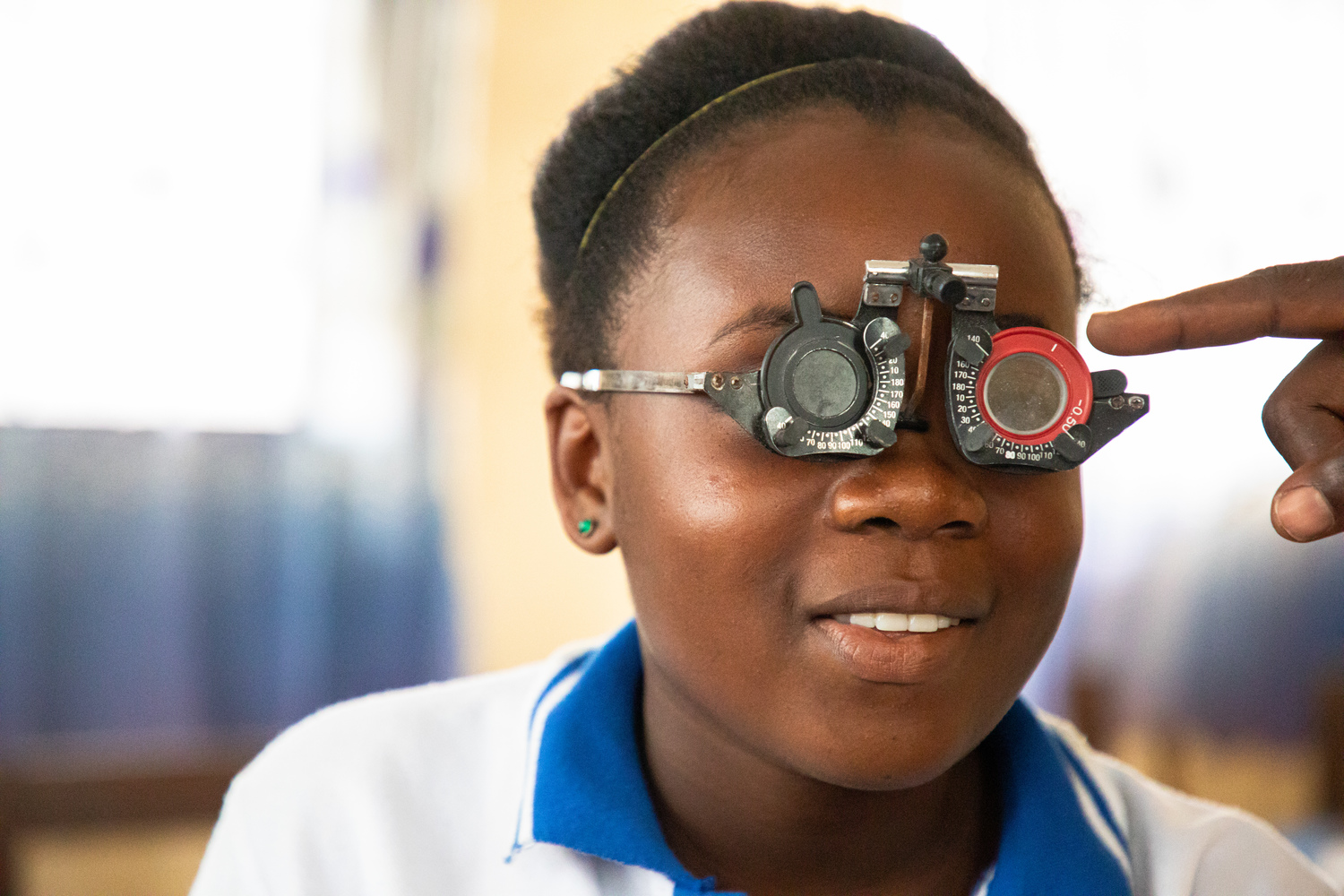 A close up of a girl shown having her eyes checked.
