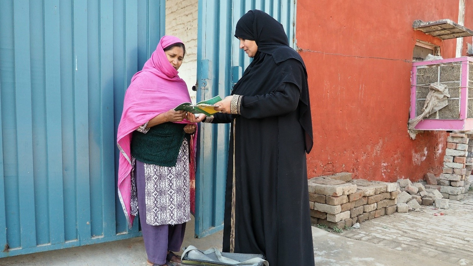 A Lady Health worker in pakistan handing out information.