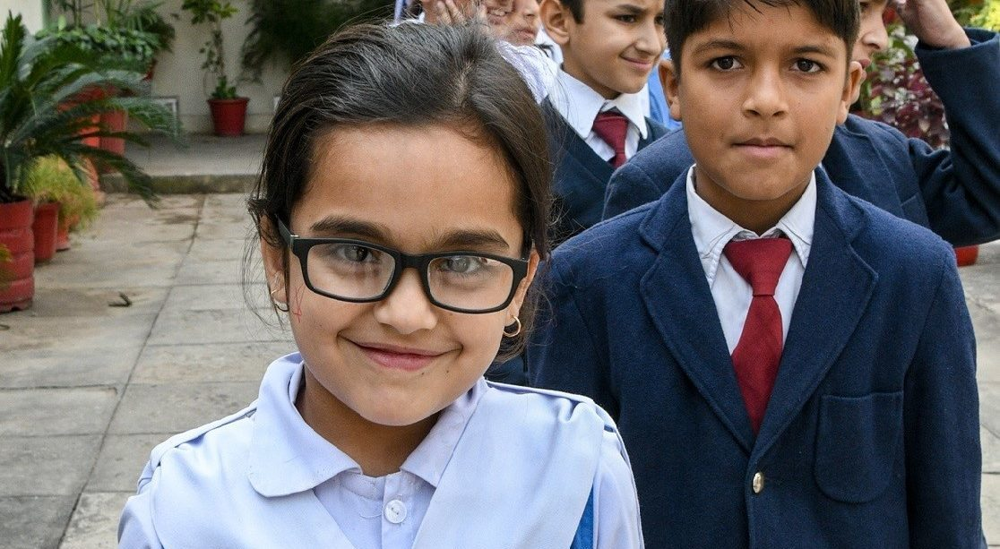A girl and a boy smile at the camera. The girl is in front and wears glasses.