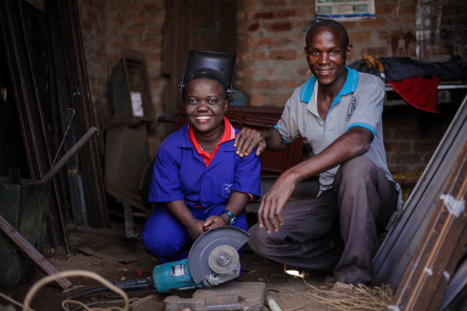 Friday Rosemary a beneficiary of Sightsavers Economic Empowerment Project, photographed with her trainer, at the shared welding workshop in Kiryandongo, Uganda.