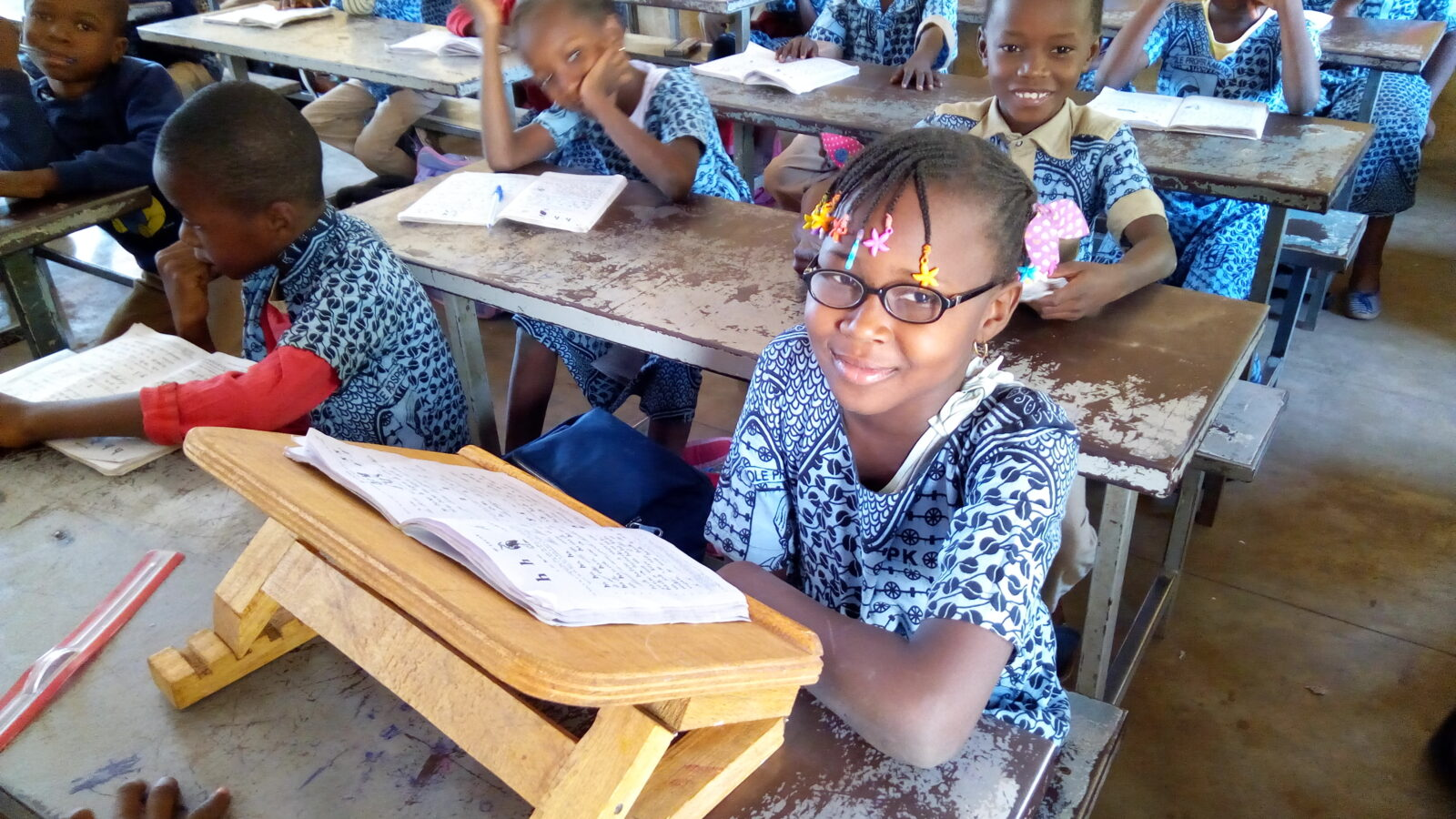 A young girl is sitting at a desk in a classroom with other pupils.