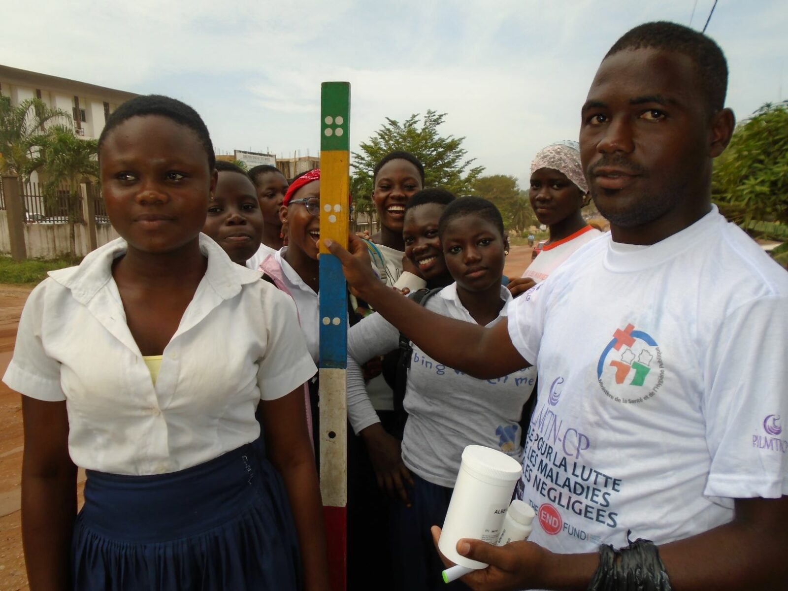 A man holds up a dosing pole, next to a woman who will be receiving medicine for onchocerciasis..