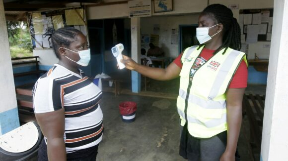 A woman wearing a high-visibility jacket checks the temperature of another woman. Both are wearing masks.