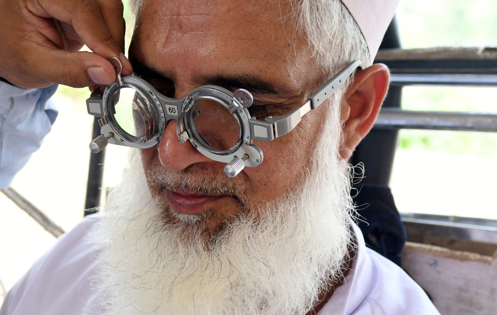 An elderly man with a grey beard tries on glasses as part of an eye test.
