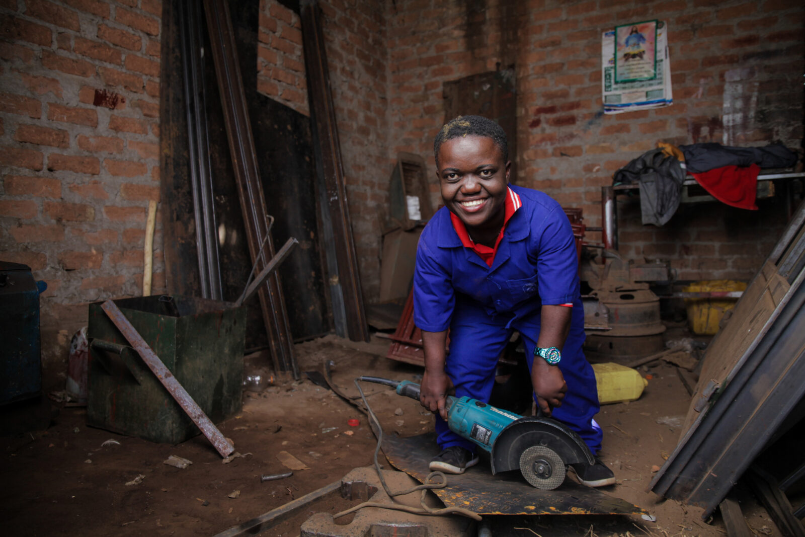 A man with dwarfism is pictured in a workshop, smiling as he uses a saw to cut a piece of metal.