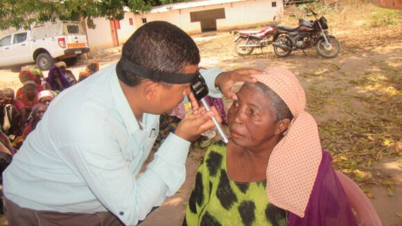 A doctor checks a woman's eyes for cataracts outdoors on a sunny day, with low cream-coloured houses in the background.