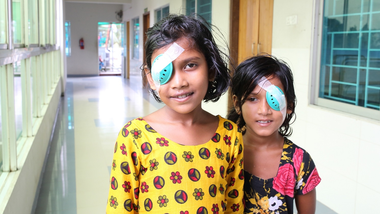 Two young girls stand together in a hospital corridor. Both are wearing colourful clothes, and have smiles on their faces. Both were wearing temporary eye patches after receiving eye surgery.