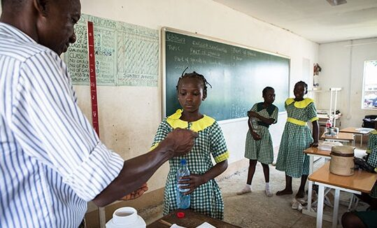 Several schoolgirls with green gingham dresses are pictured in a classroom next to a blackboard. A man is giving one of the girls some medication. She has a water bottle in hand, ready to swallow the medication.
