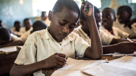 A boy sits at a desk, his head bent over his schoolbook, writing something with a pencil. Around him sit other schoolchildren.